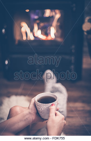 woman-sitting-in-front-of-a-wood-burning-stove-with-a-cup-of-coffee-fdk755
